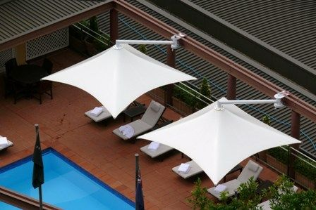 Architectural shade umbrellas cantilever over California pool deck.