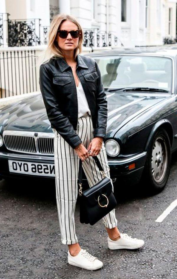 Street style look com calca listrada, blusa branca, jaqueta couro preta e tênis branco.