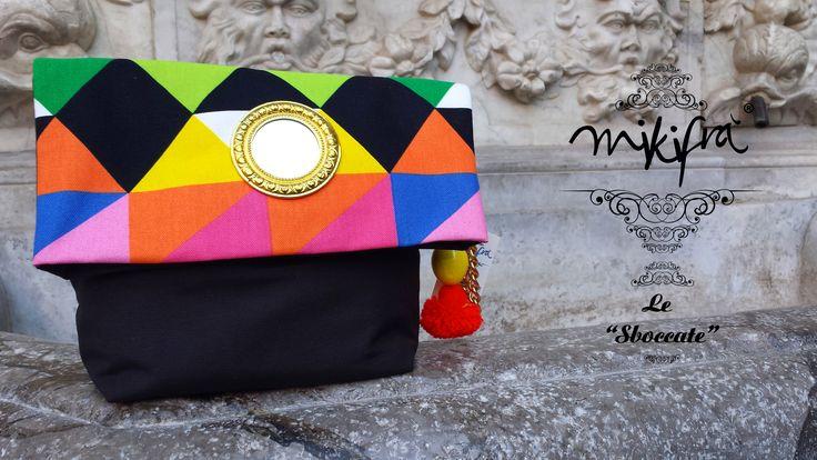 Bags Ciancianella: Bag in cotone nero e cotone colorato a fantasia triangolare. Decorazione con specchietto centrale in stile siciliano. Manichetto gioiello con ceramiche colorate, pon pon cipollotto siciliano e catena dorata.