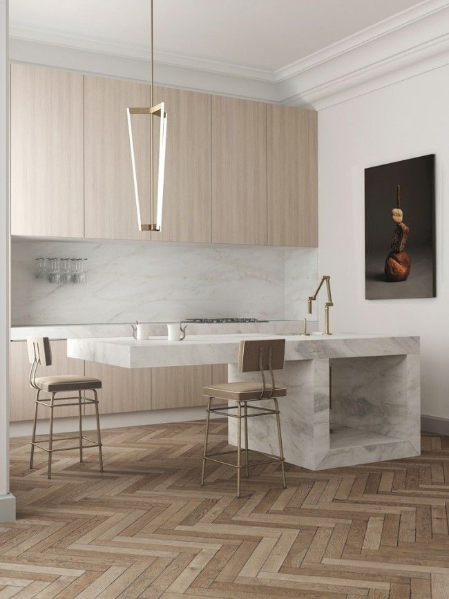 A bright and modern marble kitchen with herringbone wood floor and minimalistic furnishing by Katty Schiebeck.