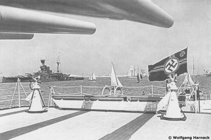 A view aft of Admiral Graf Spee. The barrels from the B turret can be seen at the top of the photo. Notice the two 2 cm light anti-aircraft gun mountings and the big naval ensign. The ship to the left is the British battleship H.M.S. Resolution.