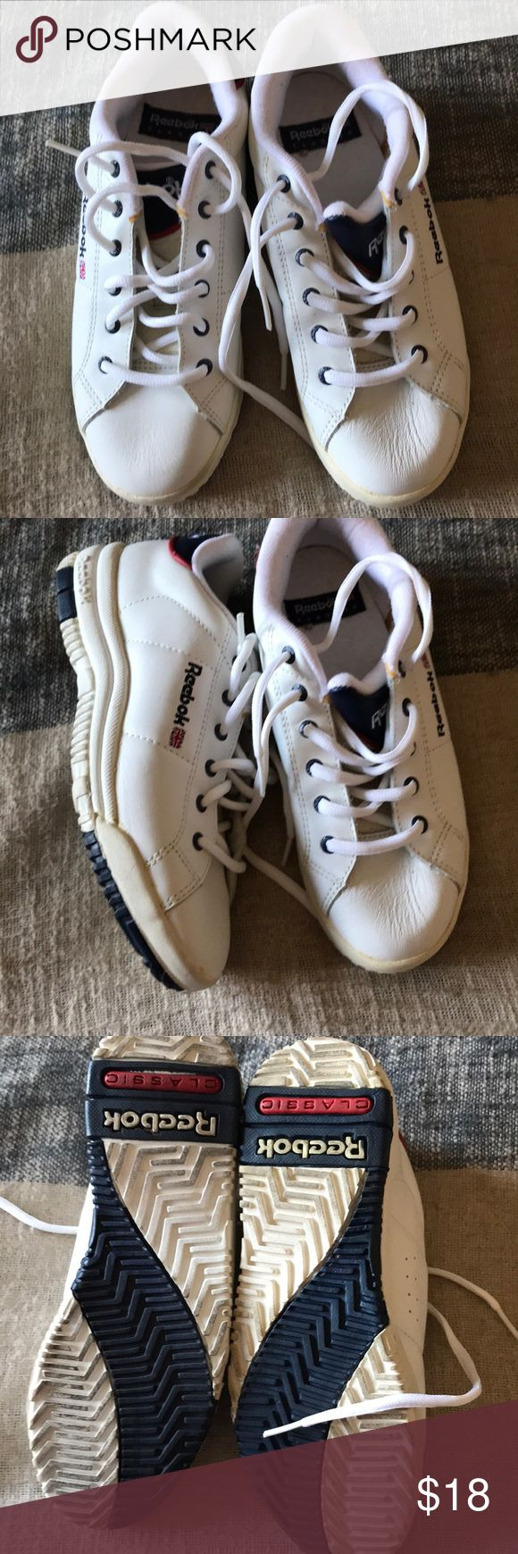 Like new REEBOK gym shoes Size 6 1/2 unisex REEBOK gym shoes. Never worn. Perfect soles. White shoe with navy tongue on shoe. Reebok symbol on side. Left tongue shoes done leather cracking underneath the laces (evident in last picture) Reebok Shoes Sneakers