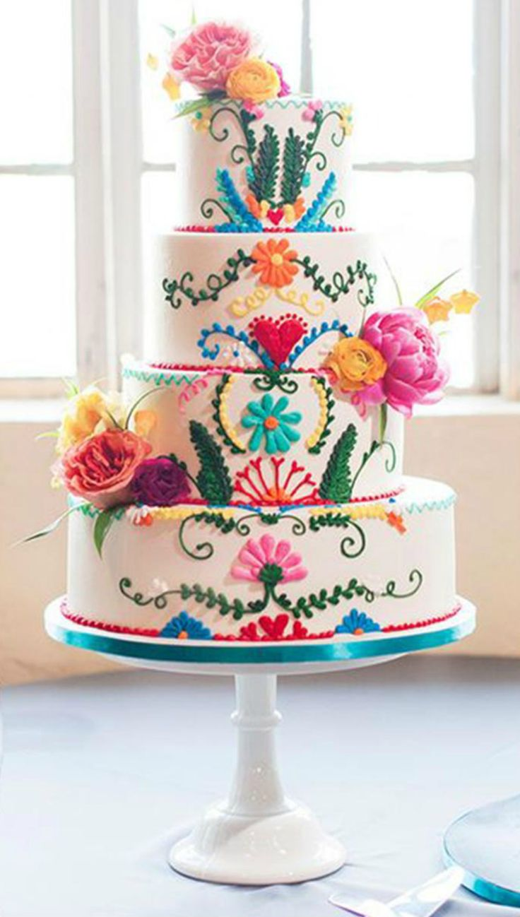 Colourful Fiesta Cake : Featuring a gorgeously embellished vanilla confection, the floral patterns and bright colours give this traditional classic a modern twist.