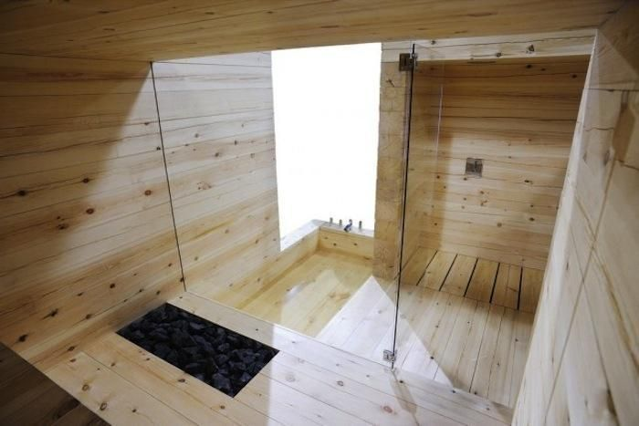 The bathing area and sauna are separated by a glass wall and door.