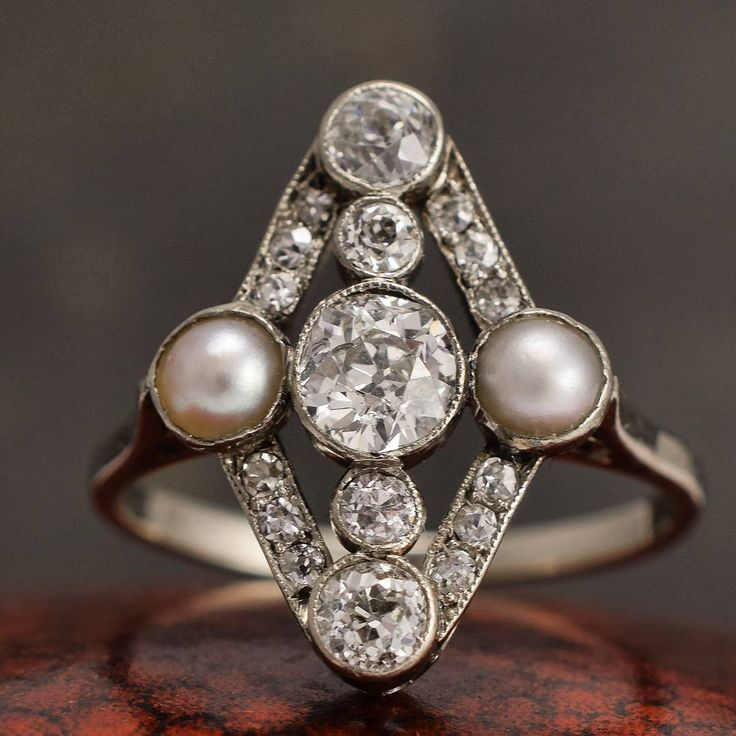 This stunning #antique cluster ring is set with two natural #pearls, and over a carat of old cut #diamonds - arranged in a rhombus shape, around a central .58ct #diamond. The settings are fashioned from #platinum, and feature lovely #millegrain detailing, while the band is modelled in 18ct white gold. An elegant and delicate ring, with lustrous pearls in remarkably good condition. It dates to c.1910. #antiquejewelry #diamondring #EdwardianJewelry #butterlaneantiques #antiqueengagementring…