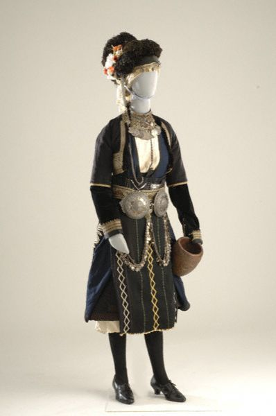 Bridal costume in the Roumlouki district (now Alexandria, near Thessaloniki). The chemise is of white cotton or silk and the quilted black coat was worn only by brides. The blue cotton sayias has gold-embroidered velvet on its two inside panels. Indispensable accessories to the bridal costume are the broumanika, armlets worn under the zaketo. The main feature of the costume is the unusual headdress, the katsouli me tis fountes (hood with pompoms), which resembles a helmet.