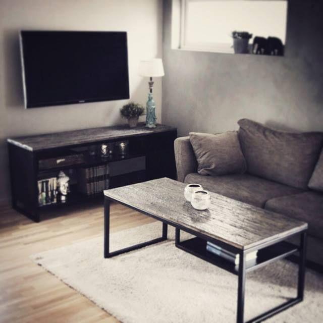 Tv-benk og sofabord laget av stål lakkert i sort og treplater.