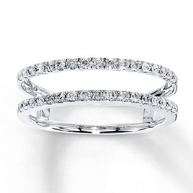 Crafted of 14K white gold, this enhancer ring is a beautiful way to complete her bridal set. Round diamonds shimmer above and below a space to insert her engagement ring, sold separately. The enhancer ring has a total diamond weight of 1/4 carat. Diamond Total Carat Weight may range from .23 - .28 carats.