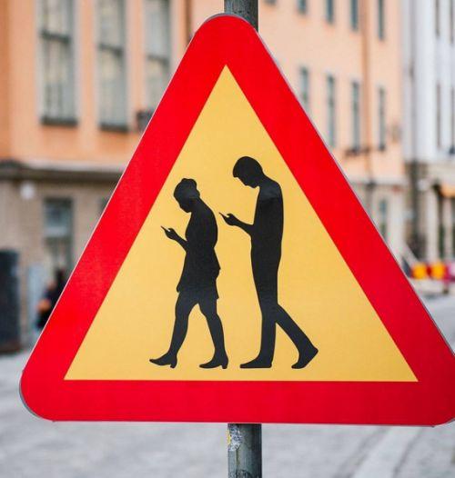 Una señal de tráfico advierte a los conductores que pueden encontrar peatones que están profundamente absortos en sus smartphones, en Estocolmo, Suecia el 2 de febrero de 2016. Crédito: AFP / Jonathan NACKSTRAND / @theeconomist