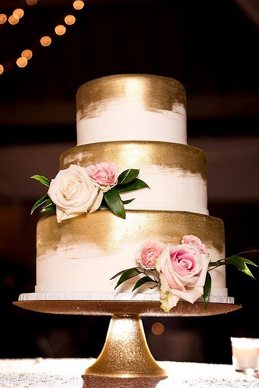 Painted gold on a wedding cake adorned with florals. View the full wedding here: http://thedailywedding.com/2016/06/04/glamorous-floral-wedding-abbey-matt/