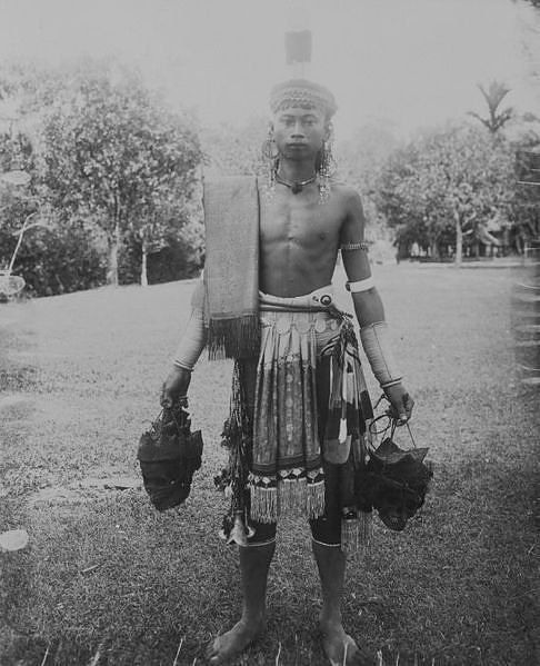 Dayak warrior with human head trophies, Indonesia.