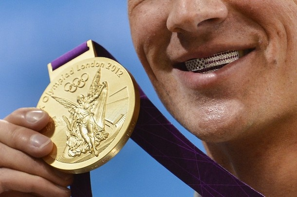 US swimmer Ryan Lochte poses with his dental braces bearing the US flag and his gold medal after winning the men's 400m individual medley swimming event at the London 2012 Olympic Games on July 28, 2012 in London.