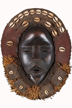 Africa |  Dan Mask with Cowry Shells. | This mask is a female mask, Glen Mu, and is used exclusively in dances at ceremonies. |  It is made of hard wood surrounded with cloth over which a smooth patina coat is applied to give a smooth skin to achieve a strong aesthetics preferred by the Dan tribe.