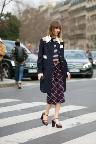 Let these Parisian street style stars inspire your holiday wardrobe: a plaid skirt.