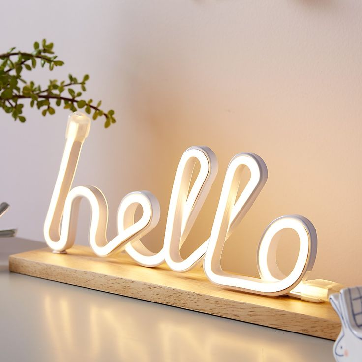 """Shop Hello Light Up Sign. Send a greeting that really illuminates the room with this unique tabletop light. Great for desks and dressers, it features LED tube lighting that spells out the word """"Hello"""" above a wood base."""