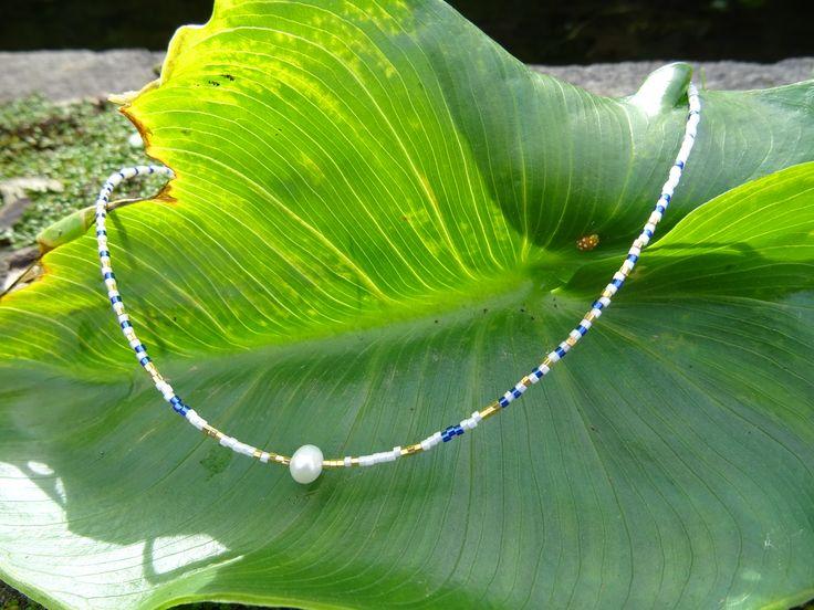 Pièce unique faite main. Collier en perles Miyuki marines, blanches et plaquées or 24 carats. La perle centrale est une perle d'eau douce forme baroque de taille 6 x 8 mm. Longueur du collier : 44 cm. Il existe le bracelet assorti dans la boutique. Les perles Miyuki sont des petites perles en verre Japonaise qui ont une forme très régulière.