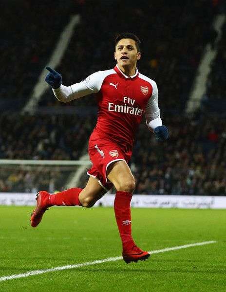 Alexis Sanchez of Arsenal celebrates as his free kick deflects off James McClean of West Bromwich Albion for their first goal during the Premier League match between West Bromwich Albion and Arsenal at The Hawthorns on December 31, 2017 in West Bromwich, England.