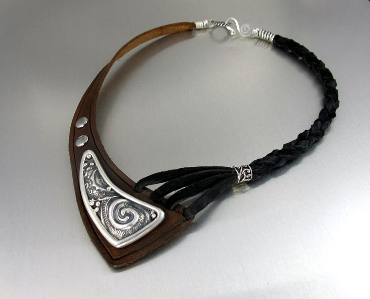This piece is made with fine silver metal clay and leather. --Lisa Barth
