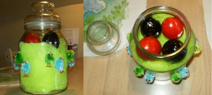 A decoration with yellow tulle and painted eggs inside a glass jar and green and blue chickens glued on the outside.