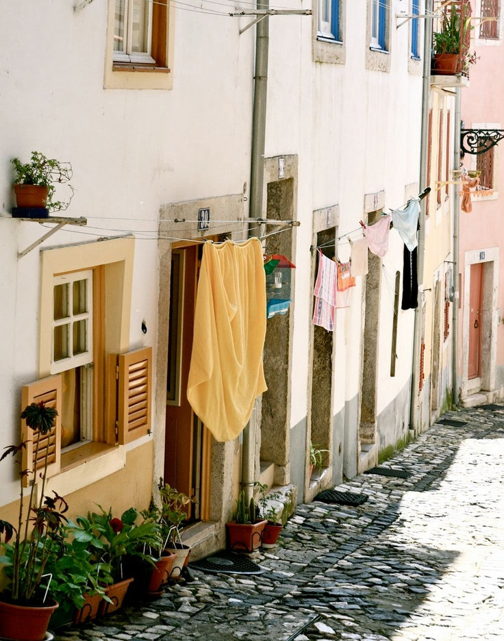 Cobblestones, laundry hanging from lines between colorful buildings | Lisbon