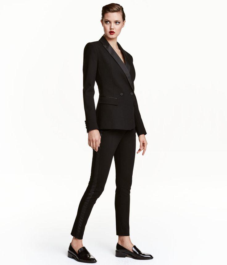 Svart. En kostymbyxa i stretchig, vävd kvalitet med detaljer och revärer i satin. Hög midja och smala ben. Knäppning med hake och hyska fram. Passpoalfickor