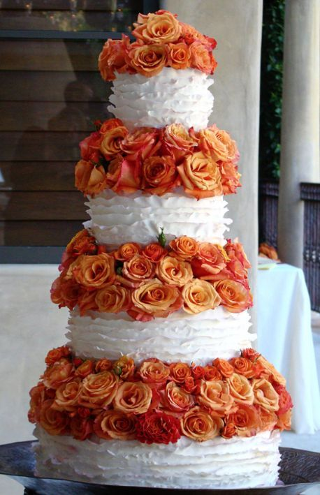 White textured wedding cake wrapped with orange flowers; Featured Cake: The Butter End Cakery