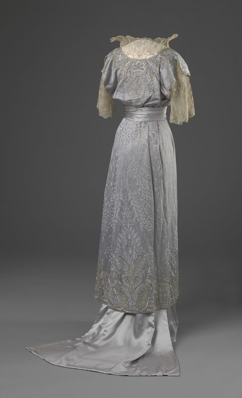 Lovely 'mist gray' gown (1910)  The overskirt layer is embroidered with silver thread.  The squared train is satin.  The bodice is slightly bloused, and bears a lace, flared stand up collar.  Waist is wrapped with satin band