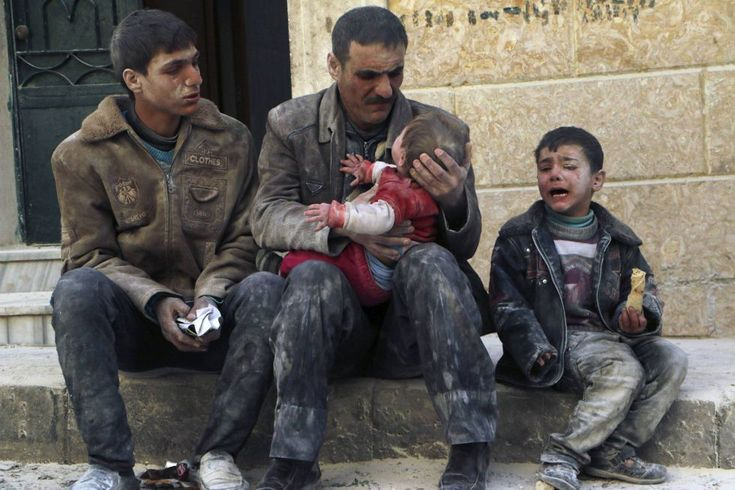 A man holds a baby who has just been rescued from under the rubble after an air attack by forces loyal to Syrian President Bashar al-Assad in Aleppo Masaken Hanano. February 15, 2014.