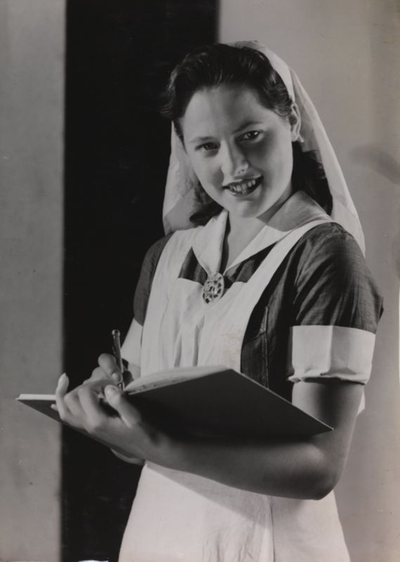 A nurse writing in a book, taken by Photographic Advertising Limited, c. 1950.