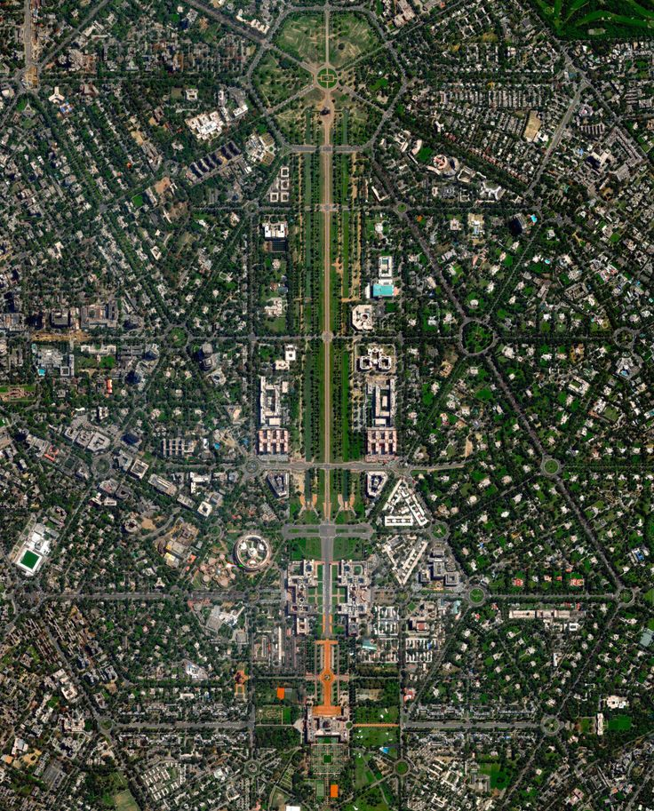 dailyoverview: New Delhi serves as the capital of India and is home to more than 21 million residents in its metro area. Officially inaugurated in February 1931, the city was planned by British architects Sir Edwin Lutyens and Sir Herbert Baker. Their design centered around two promenades - the Rajpath and the Janpath - that run perpendicular to each other and intersect here at center. For a sense of scale, this Overview shows approximately four square miles. 28.613025571°, 77.225124376°