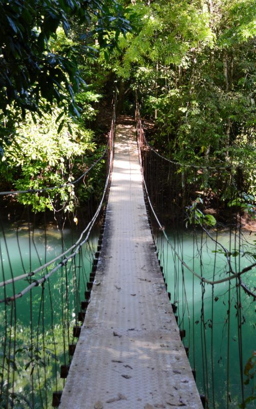 Bridge over the Rio Aguijitas near Drake Bay on Costa Rica's nature-rich Osa Peninsula. This suspension bridge connects a trail that leads from the village to eco-lodges and even more remote locations to the south. You often see kayakers out enjoying this river's strikingly blue water.