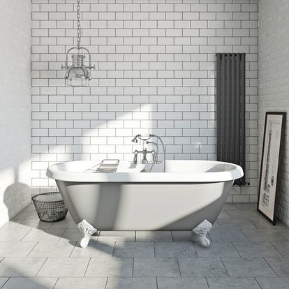 Grey painted roll top bath with metro tiles and industrial interior