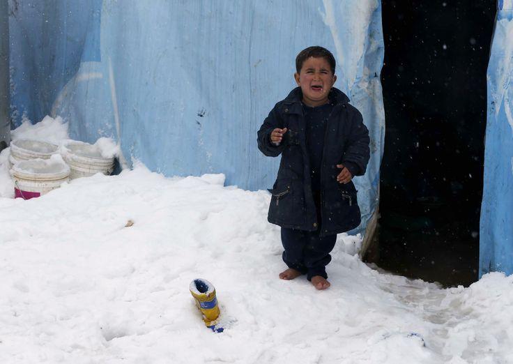 Seorang anak pengungsi Suriah menangis saat berdiri tanpa sepatu di atas salju yang turun di kamp pengungsi Zahle, di Lembah Bekaa, Lebanon.
