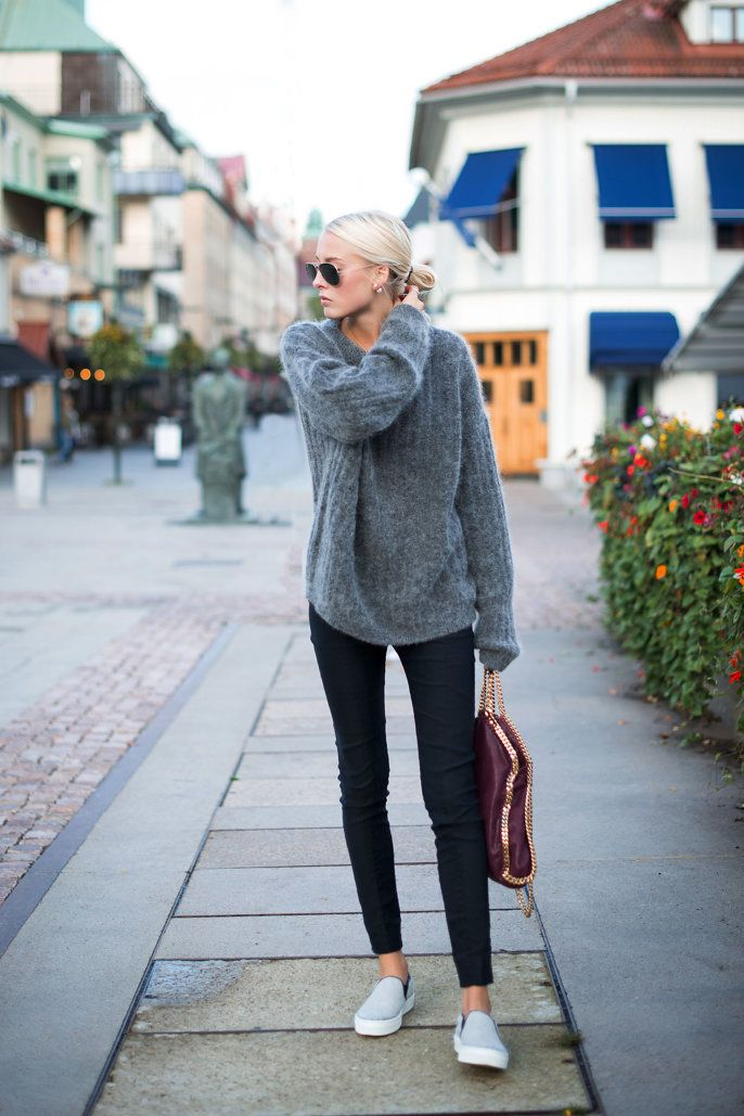 Ellen Claesson is wearing a grey top and black trousers from Acne Studios, light grey slip-ons from Céline and a bag from Stella McCartney