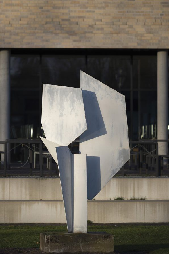 #Kiel Das Kunstwerk spielt mit den Gegensätzen zwischen den ebenen Platten und der aus ihnen entstandenen Räumlichkeit. Wie eine Blüte, die sich aus ihrer Knospe entfaltet, so wirkt auch die Entfaltung der Figur.