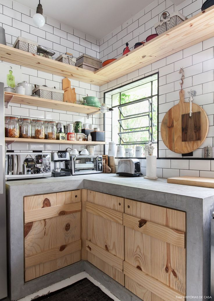 Cozinha integrada tem bancada de concreto, armários e prateleiras de pinus e subway tiles.