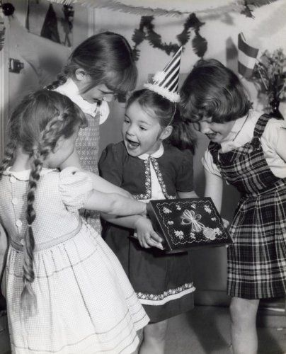 Meisje met feestmuts met vriendinnetjes om haar heen houdt een cadeau [kado] vast tijdens verjaardagsfeestje. Op de achtergrond hangen slingers en er staat een vlaggetje. Nederland, jaren '50.