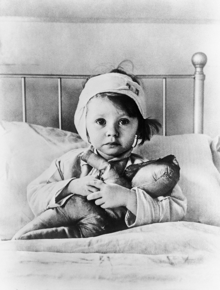 Eileen Dunne, aged three, sits in bed with her doll at Great Ormond Street Hospital for Sick Children, after being injured during an air raid, London, September 1940