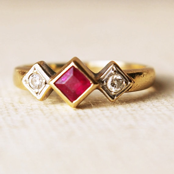 $158 This lovely vintage ring is approximately 50 years old, 9k yellow gold with two diamonds and one ruby- the diamonds are round approximately 2mm and truby is 3.5mm or 4mm tip to tip. The band width is 2mm, very thick and sturdy. Total weight 2.46 grams.