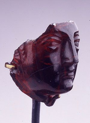 Mid-3rd C. BCE. Carved Garnet portrait. Likely Berenice II, a great beauty, muse, royal patron of the arts, embroiled in court politics; wife of the 3rd ruler of the Ptolemaic dynasty of Egypt, assasinated after his death. Hellenistic