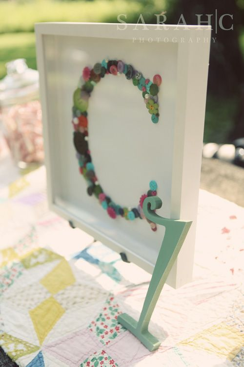 I loved this idea and used it as a centerpiece at Ava's party - I bought a mixed bag of buttons since I didn't have any colorful ones saved up to make this framed button monogram.  I painted a wooden number one and glued it to the frame.
