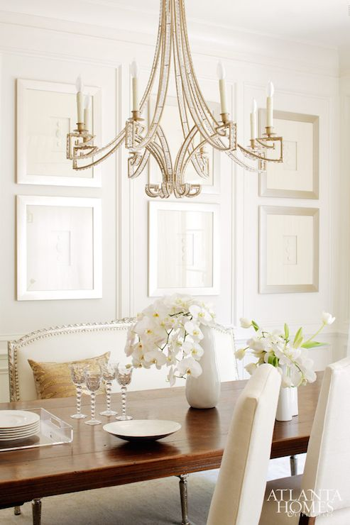 Elegant, sophisticated dining room boasts jewel encrusted chandelier illuminating long dining table lined with ivory camelback dining chairs on one side and ivory French settee on the other side placed in front of walls covered in collection of art framed in silver frames.