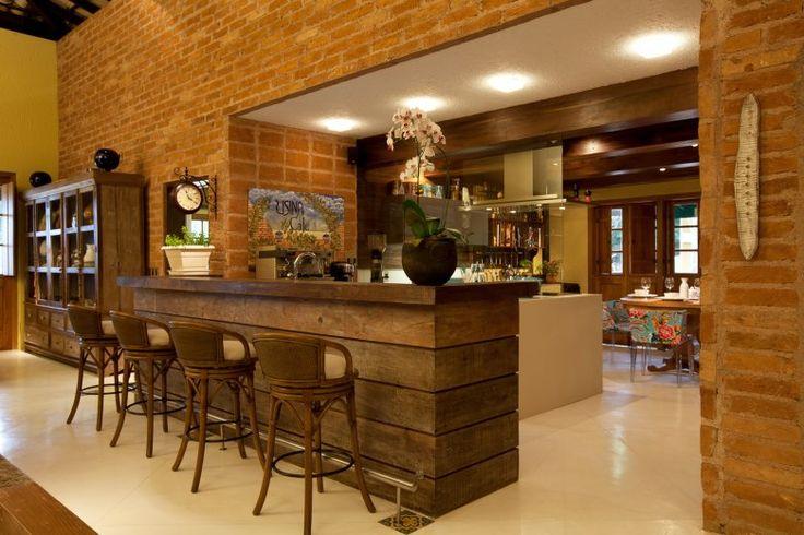 Um balcão separa o grande living da cozinha, criando um agradável e aconchegante cantinho do café. A imponente parede de tijolos de demolição se destaca no espaço.