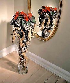 Skurrile Idee: Der Weihnachtsstern wird zusammen mit allerei Fundstücken aus dem Wald dekoriert. Verwenden Sie dafür eine hohe, schlanke Glasvase. Hinein kommen Äste, dicke Schwarzkiefernzapfen und rote Christbaumkugeln. Damit der obere Teil, der aus der Vase ragt, nicht herausfällt, werden die Zapfen mit Heißkleber aneinandergeklebt. Als Krönung kommt in die Mitte ein knallig roter Weihnachtsstern