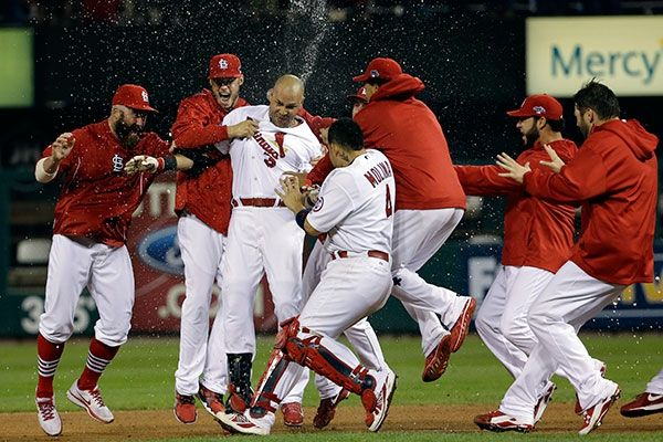 St. Louis Cardinals' Carlos Beltran is congratulated by teammates after his game-winning hit during the 13th inning of Game 1 of the Nationa...