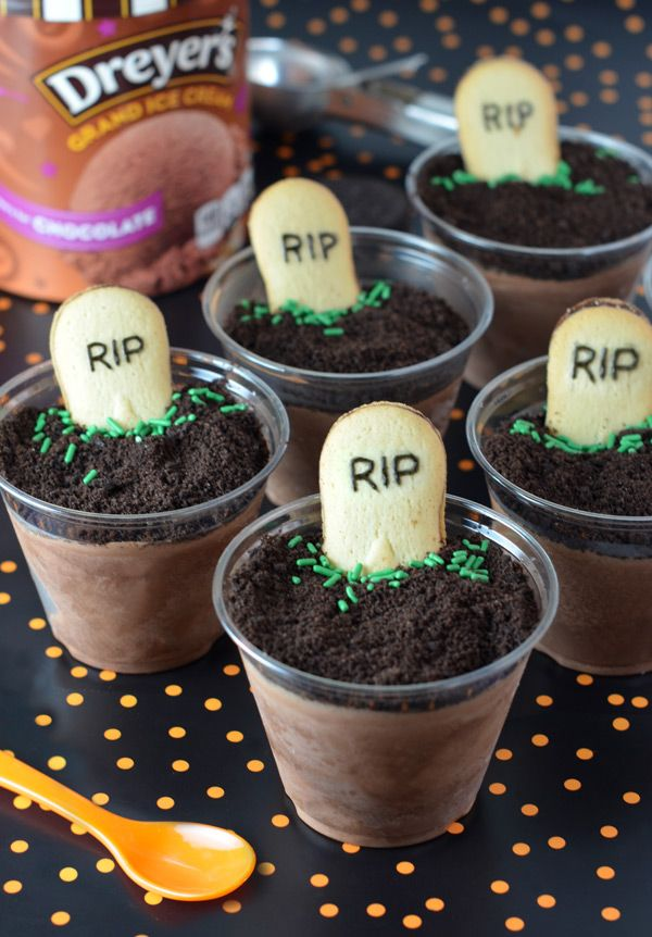 """Dreyer's Ice Cream Graveyard Cups: Add a bit of trick to your treat with these deliciously spooky ice cream graveyards. Scoop chocolate ice cream into individual cups, top with crushed cookie """"dirt,"""" and finish off with a cookie tombstone and green sprinkles for a simple dessert that'll literally have your kids screaming for ice cream!"""