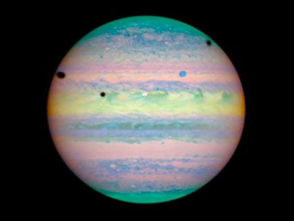 Eclipse on Jupiter with three of its largest moons; Ganymede is the blue circle and its shadow is at the left edge of the sphere, Io's  shadow is at left and Callisto's is on the right edge