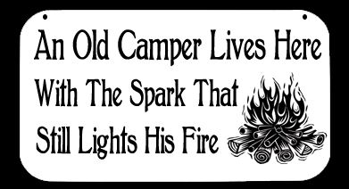 This camping sign features the words AN OLD CAMPER LIVES HERE WITH THE SPARK THAT STILL LIGHTS HIS FIRE, along with a roaring campfire.