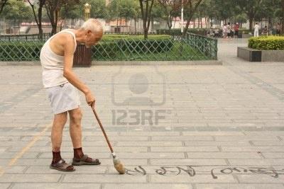 Calligrafia cinese: old man sta scrivendo Han caratteri sul terreno con pennello e acqua - 22 luglio 2010 Archivio Fotografico