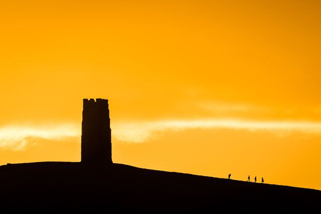 People trek from St Michael's Tower after watching the sun rise over Glastonbury Tor, Somerset, England on November 26, 2017 as forecasters issued a yellow 'be aware' weather warning for western Britain. (Photo by Ben Birchall/PA Images via Getty Images)